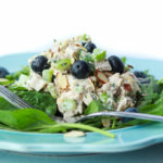 Chicken salad with blueberries and almonds over spinach.