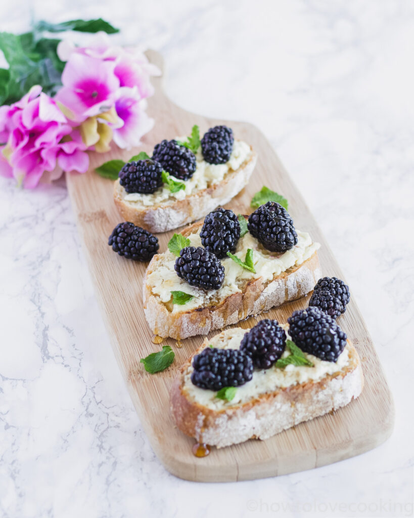 Serving board with Honey Goat Cheese Toasts with Blackberries and Mint